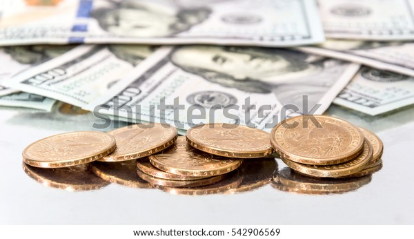 Coins with one hundred dollar bills on reflective background.