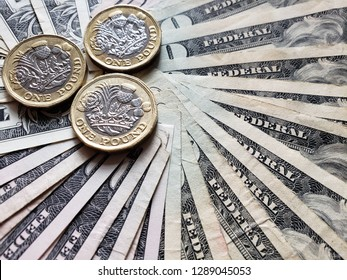 coins of one sterling pound and background with american dollars bills