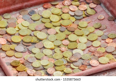 A lot of coins over a tray. Cents of euro (Fractions of 50, 20, 10, 5, 2 and 1). Outdoor scene in an overcast day.