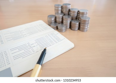 coins and pen on savings account passbook