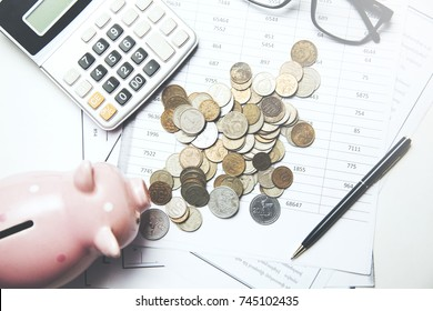 coins with piggy  bank and calculator on document