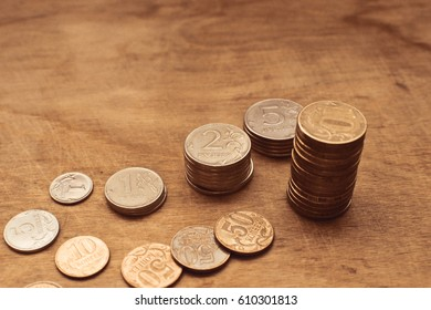 coins piles and a few coins on wooden surface