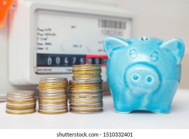 Coins and pink piggy bank near a gas meter at home. Symbolic image of cost, energy efficiency and saving natural gas at home.