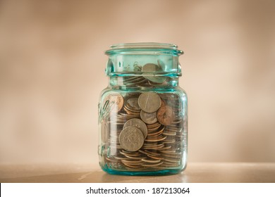 Coins in savings jar full of money