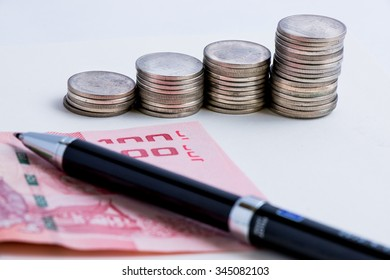 Coins setup in line graph put beside banknote. Put a pen on money, financial accounting concept.