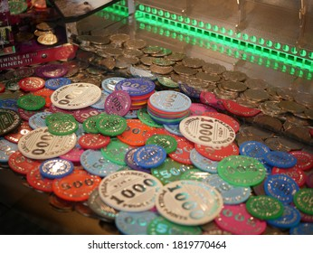 Coins in a sliding machine (coin pusher) (multiple colors) at the fairground
