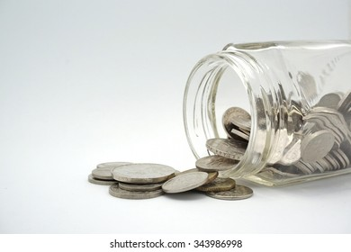 Coins spilling out of a glass bottle