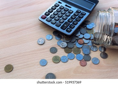 Coins spilling out of a glass bottle and calculator on wood table in morning time with financial background business concept.