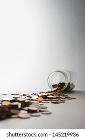 Coins spilling out of jar on its side in studio