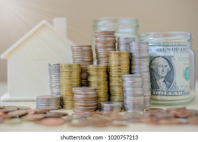 coins stack, dollar banknote and house model on wooden table in the morning sunlight. business, investment, retirement, finance and Money Saving for the future concepts