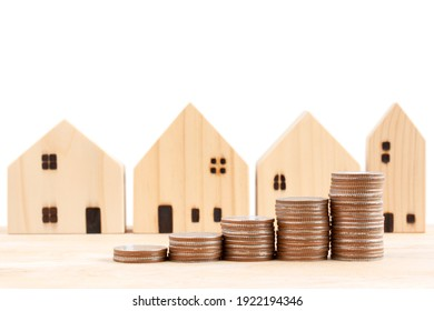 Coins stack in front of wooden houses on wooden table, to show concept saving money, prepare money for new house, family plan, home, loan, money investment concept isolated on white background.