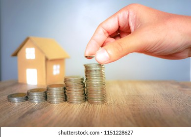 Coins stack with human hand and paper house background for saving and investment concept. House is real estate which it is asset for investing for take a profit.