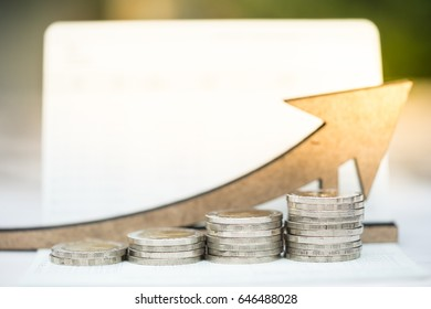 Coins stack on bankbook with arrow wooden icon. Concept of money saving, financial, personal loan,retirement,insurance.