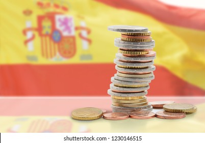 Coins stacked on each other in different positions with Spanish flag