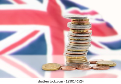 Coins stacked on each other in different positions with United kingdom flag