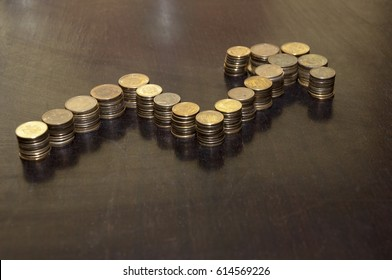 Coins stacked on each other in shape of arrow. Concept of success.
