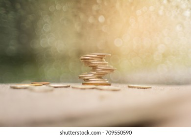 Coins stacked on each other in different positions with bokeh background. Money concept.