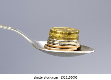 the coins are stacked on top of each other with a stack, the coins are in a metal teaspoon, the background is gray