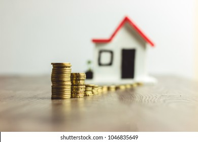 Coins stacked on top of a wooden table, with a blurred house on the background: real estate, property investment, house mortgage, savings financial concept.