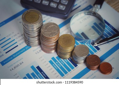 Coins stacking and chart with magnifying glass for analyzing financial report of value investor in stock market concept.