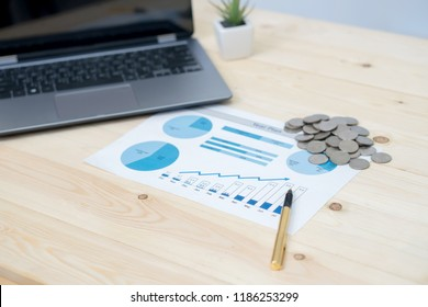 Coins stacks with notebook laptop computer and financial graph