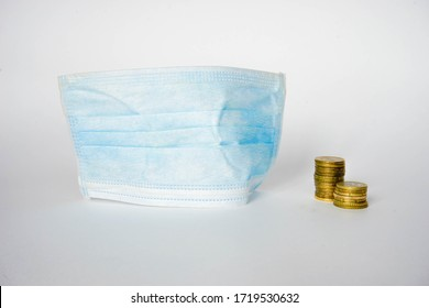 Coins stands near blue mask. A mask is needed to protect against coronavirus infection. Coins symbolize the economic crisis due to quarantine.