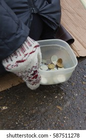 Coins of street beggar - hand in mitten holds conteiner with russian rubles, winter cold russia