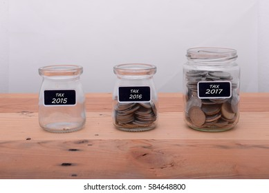 Coins tax into clear bottle on wooden background,Business investment growth concept.