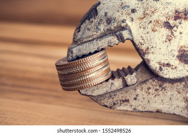 Coins tightened up in clamp wrench. Inflation, economy or financial crisis, trade war concept. Inflation rate is price increase of service and goods in an economy over a period of time.