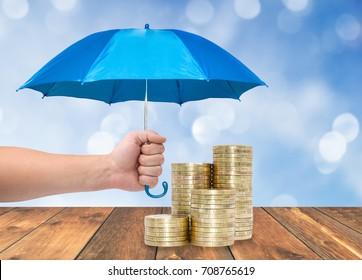 Coins under a blue umbrella protection money concept
