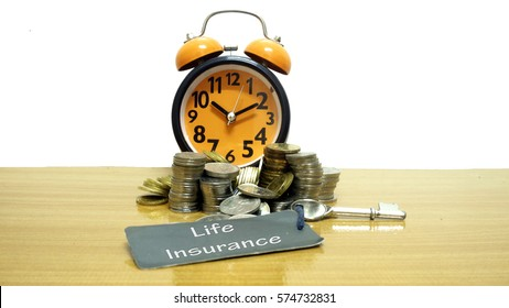 coins, watches and keys on wooden table with word Life Insurance