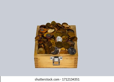Coins in a wooden box on a white background