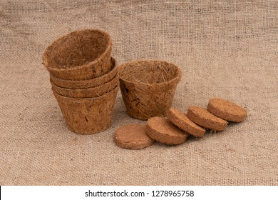 Coir plant pots and compressed compost on hessian. Environmentally friendly spring gardening.