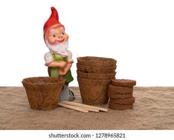 Coir plant pots and compressed compost with wooden labels and generic garden gnome. Environmentally friendly spring gardening. Isolated on white background.