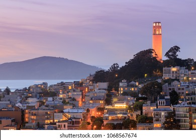 Coit Tower on Telegraph Hills and San Francisco Bay with Angel Island in the background at dusk. Taken from a downtown building rooftop. San Francisco, California, USA.
