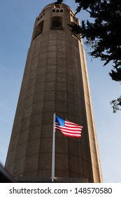 Coit Tower rises into blue San Francisco sky with American Flag in foreground