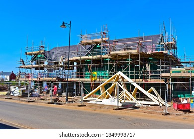 Coity, Bridgend County Borough / Wales UK- 3/24/2019: New Homes under construction. Building site with partially completed houses surrounded by scaffolding.
