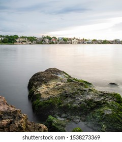 Cojimar, Havana, Cuba. August 24 2019. A rock in the foreground and a partial view of small coastal town in the background.