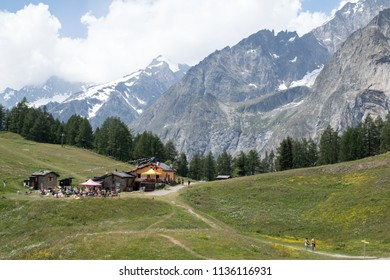 Col Checrouit, Italy - July 15, 2018: A trekking trail of the Tour du Mont Blanc trail (TMB) with a view on La Maison Vieille refuge and the South side of the Mont Blanc massif in summertime