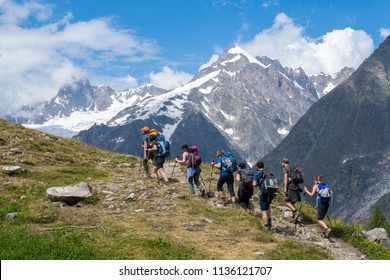 Col Checrouit, Italy- July 15, 2018: People hike on the mountain trekking trail of the Tour du Mont Blanc trail (TMB) with a view on the South side of the Mont Blanc massif in summertime
