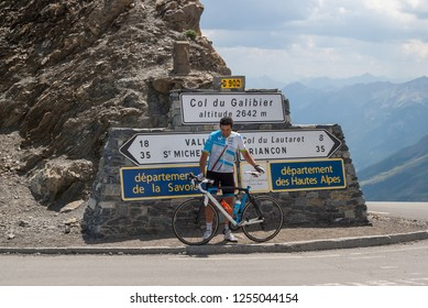 Col du Galibier/French Alps/France-July 30, 2018  The cyclist poses for a photo along with his bicycle in front of the signposts of the iconic Аlpine Pass of the Col du Galibier in the French Alps.