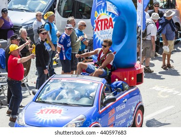 COL DU GLANDON, FRANCE - JUL 23:Man throwing promotional stuff  during the passing of the Publicity Caravan on the road to Col du Glandon in Alps in the stage 18 of Le Tour de France on July 23, 2015