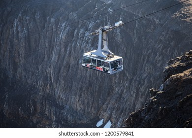Col du Pillon, Vaud / Switzerland - September 17th 2018: Cable car in the mountains. Funicular with a big rockface in the background. High mountains in the alps. Public transport in Switzerland.