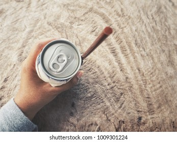 Cola can with drinking straw on hand