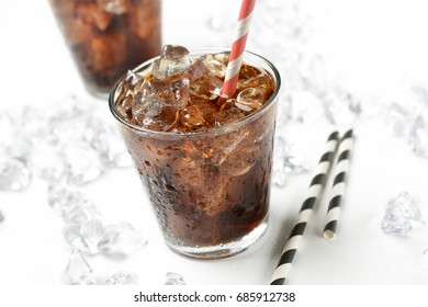 Cola with crushed ice in the glass on white background - closeup