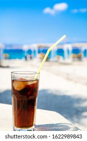 Cola drink (Cuba Libre cocktail) in the sunny beach. Leisure vacation concept. Summertime.