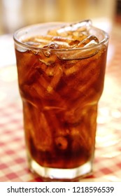 Cola in drinking glass with ice on resturant table with blurred background.Sweet sparkling carbonated drink beverage fast food with big calorie. Selective Focus.