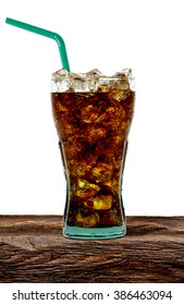 Cola in glass on wooden table with crushed ice and straw on white background