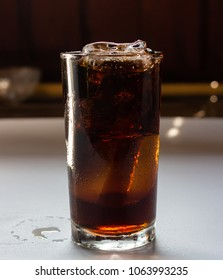 Cola with ice in glass on white table