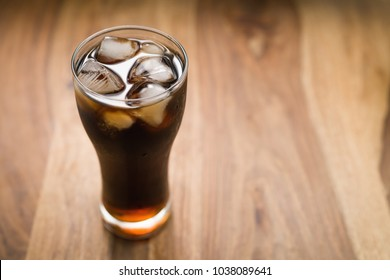 cola with ice in glass on wood table